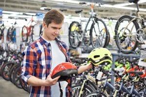 Mann wählt richtige Fahrradhelm-Größe