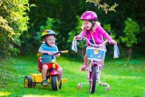 Geschwister fahren Fahrrad mit Helm