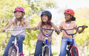 Drei Mädchen mit Fahrradhelmen und Rädern