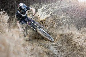 Mountainbiker mit Fullface-Helm im Schlamm