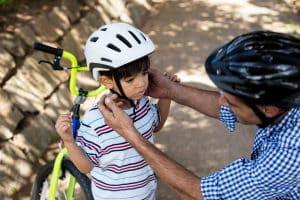 Vater justiert Fahrradhelm von Sohn